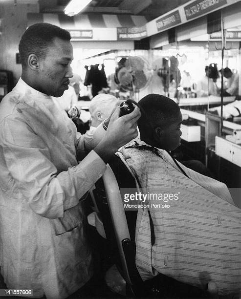 An African American barber cutting the a boy's hair in a Harlem shop New York February 1956