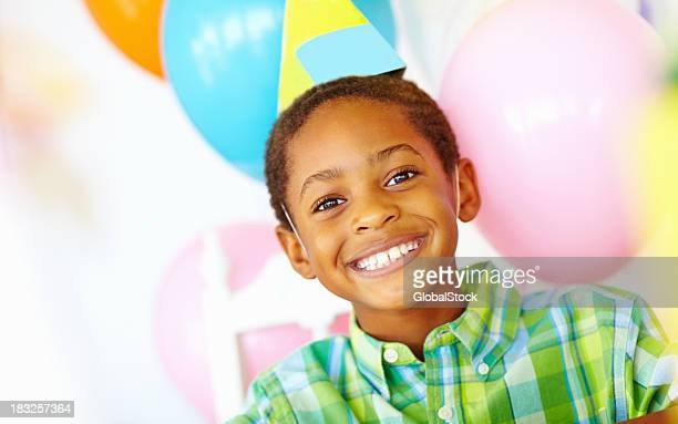 An African American birthday boy with balloons in the background