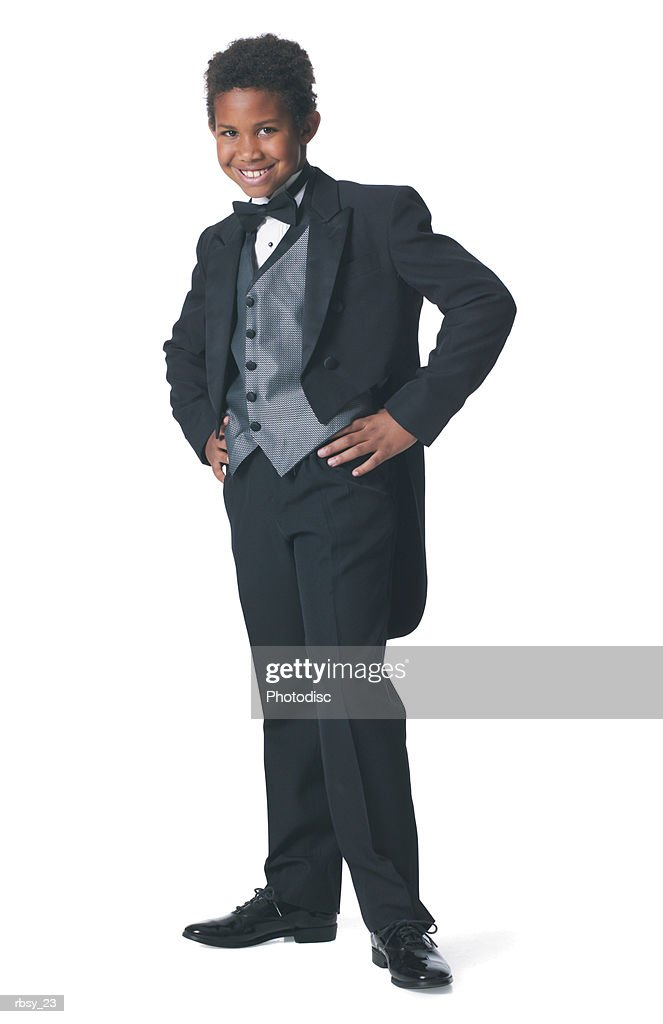 an african american boy dressed in a tuxedo puts his hands on his hips and smiles : Foto de stock