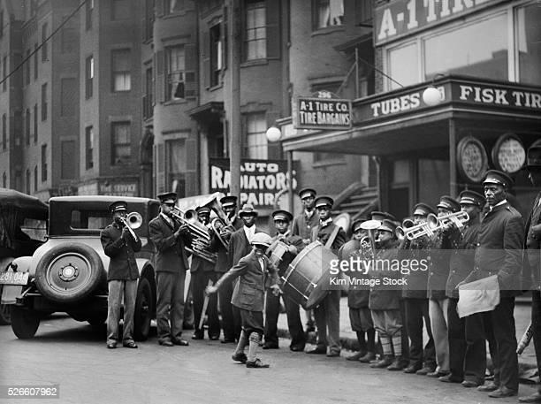 An African American boy street dances to a brass band
