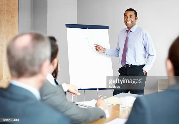 An African American business man giving presentation in meeting