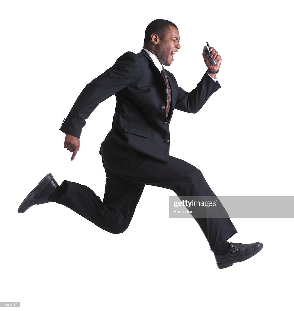 an african american business man holds a cell phone and leaps through the air : Foto de stock