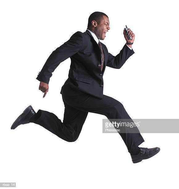 an african american business man holds a cell phone and leaps through the air