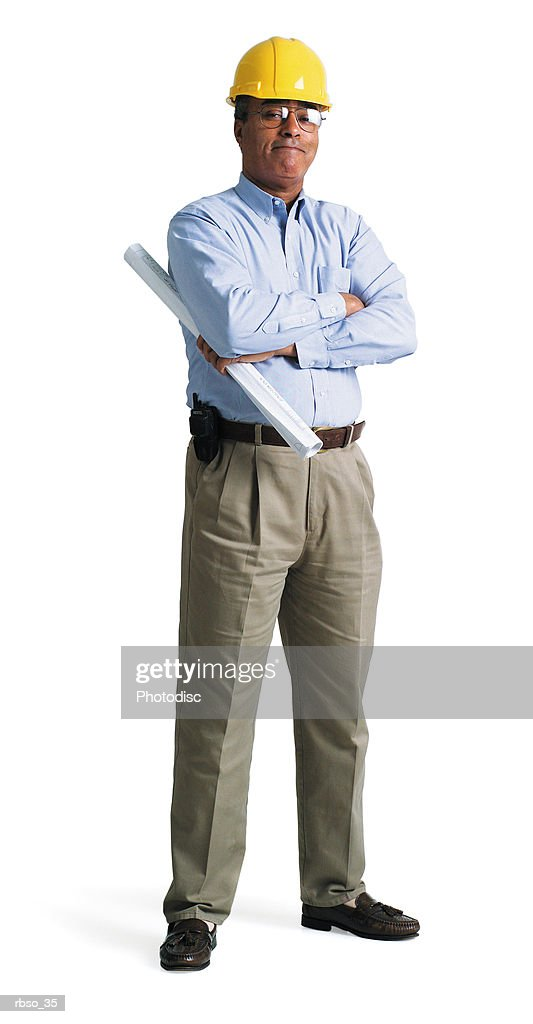 an african american contractor dressed in a dress shirt and hard hat stands holding his plans : Foto de stock