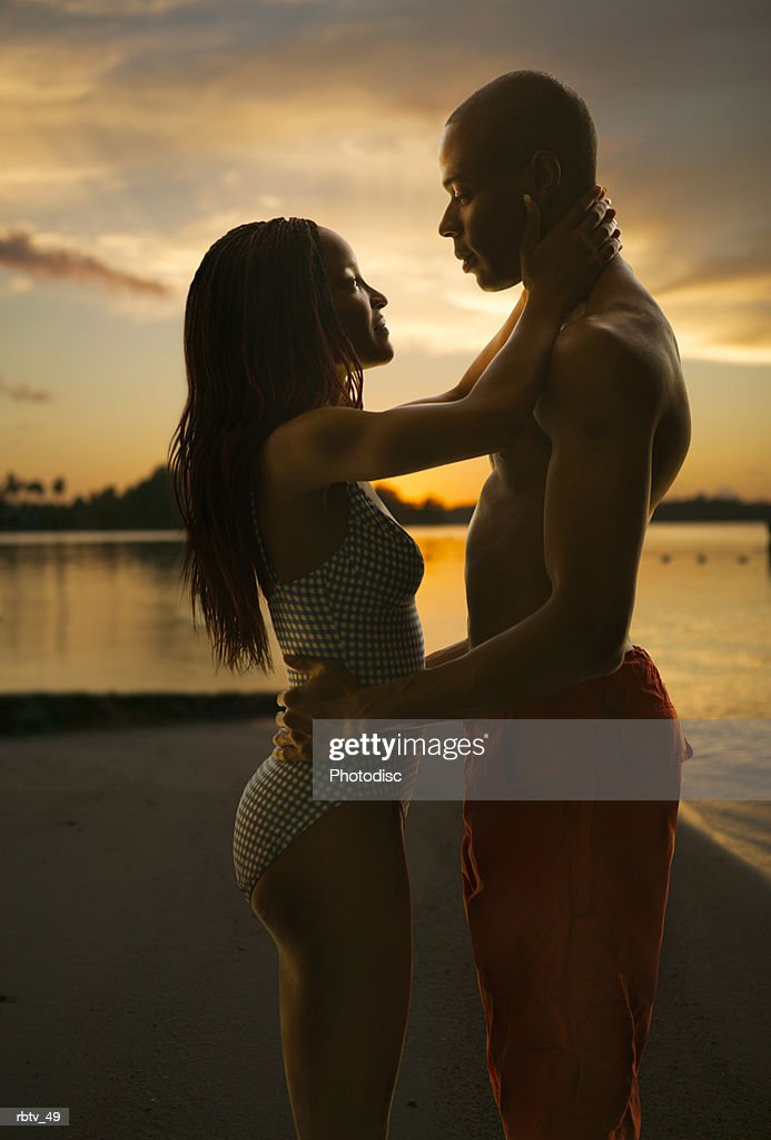 an african american couple in swimsuits embrace lovingly on a beach at sunset : Foto de stock