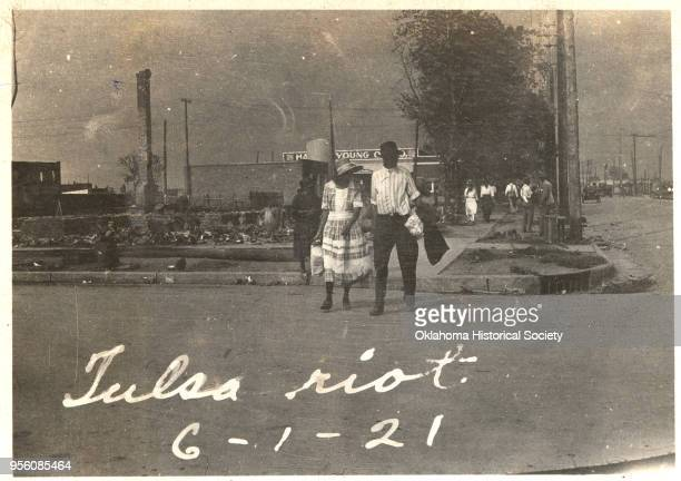 An African American couple walking across a street with smoke rising in the distance after the Tulsa Race Massacre, Tulsa, Oklahoma, June 1921.