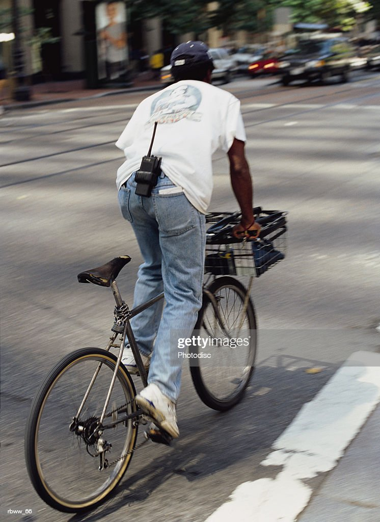 an african american courier rides a bike to deliver a package : Foto de stock