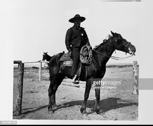 An African American cowboy sits saddled on his horse in Pocatello At the crossing of the Oregon Short Line and the Utah and Northern railroads...