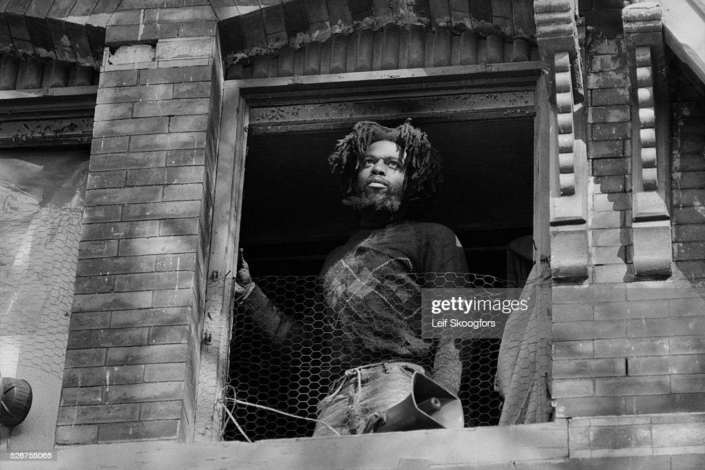 An African American cult member of MOVE, founded by John Africa, stands in the window of their barricaded house in the Powelton Village section of Philadelphia, Pennsylvania.