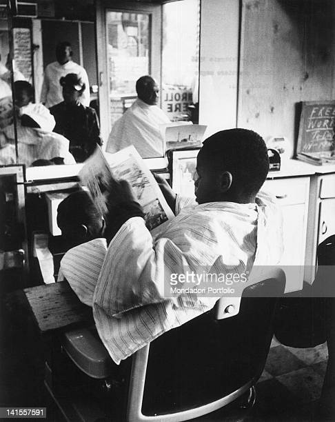 An African American customer reading the newspaper seated in a barber's chair in Harlem New York February 1956
