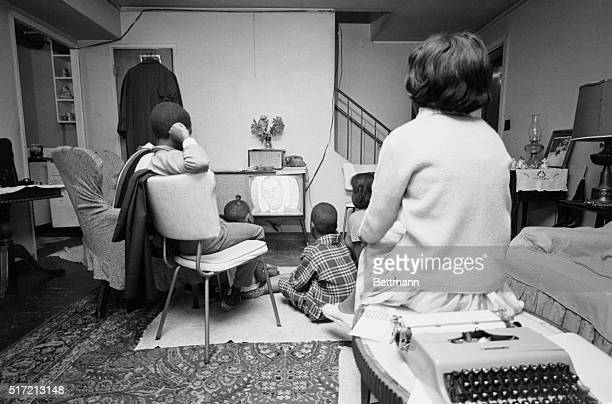 An African American family watches President Lyndon B Johnson on television speaking before a joint session of Congress on the African American's...