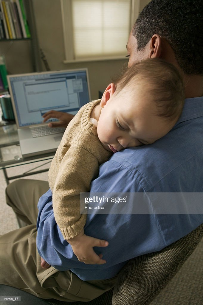 an african american father sits and works at his computer while holding his baby son : Stockfoto