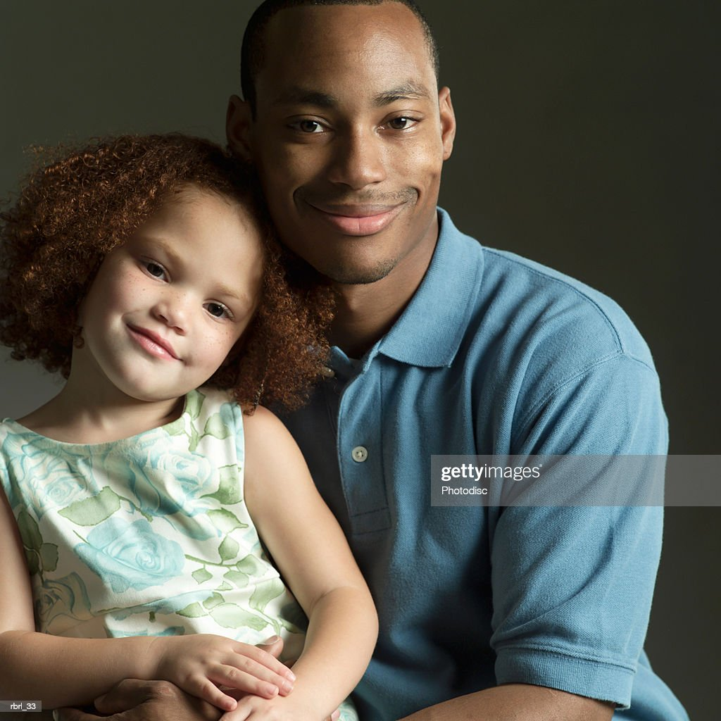 an african american father smiles as he hugs his young daughter : Stockfoto
