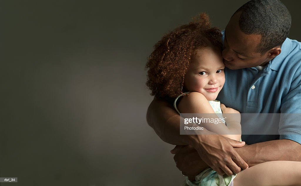 an african american father turns as he kisses and hugs his young daughter : Foto de stock