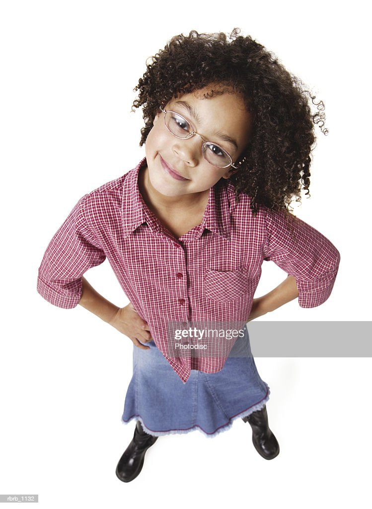 an african american female child in a jean skirt and a red plaid shirt puts her hands on her hips and smiles up at the camera : Stockfoto
