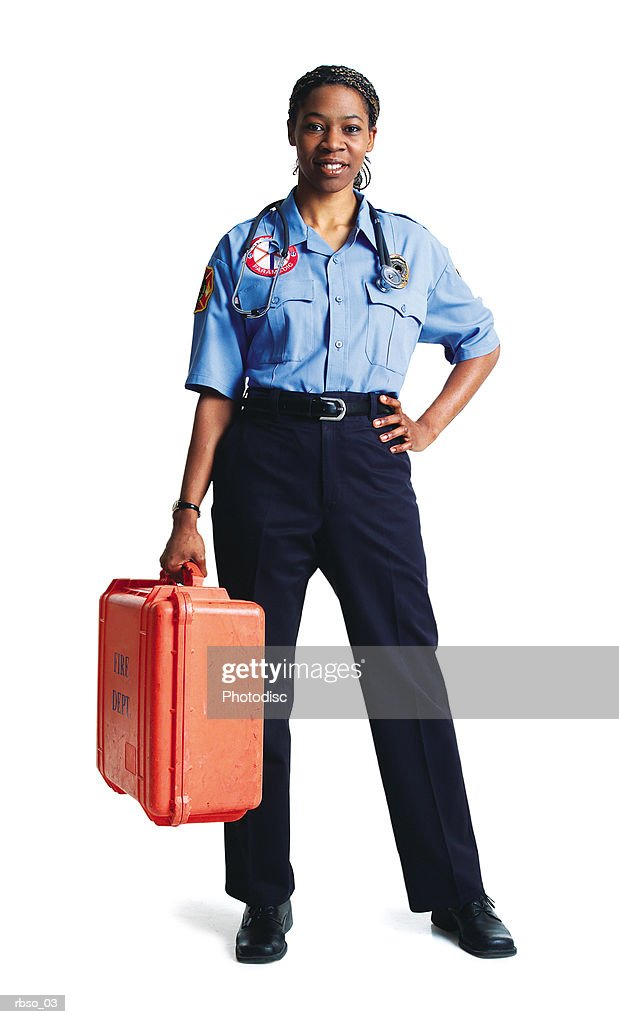 an african american female paramedic stands in uniform holding her gear : Foto de stock