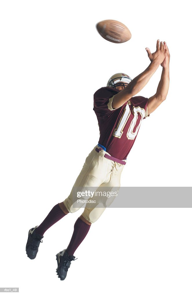 an african american football player in a red and white uniform is jumping up with arms outstretched to catch a football : Stockfoto