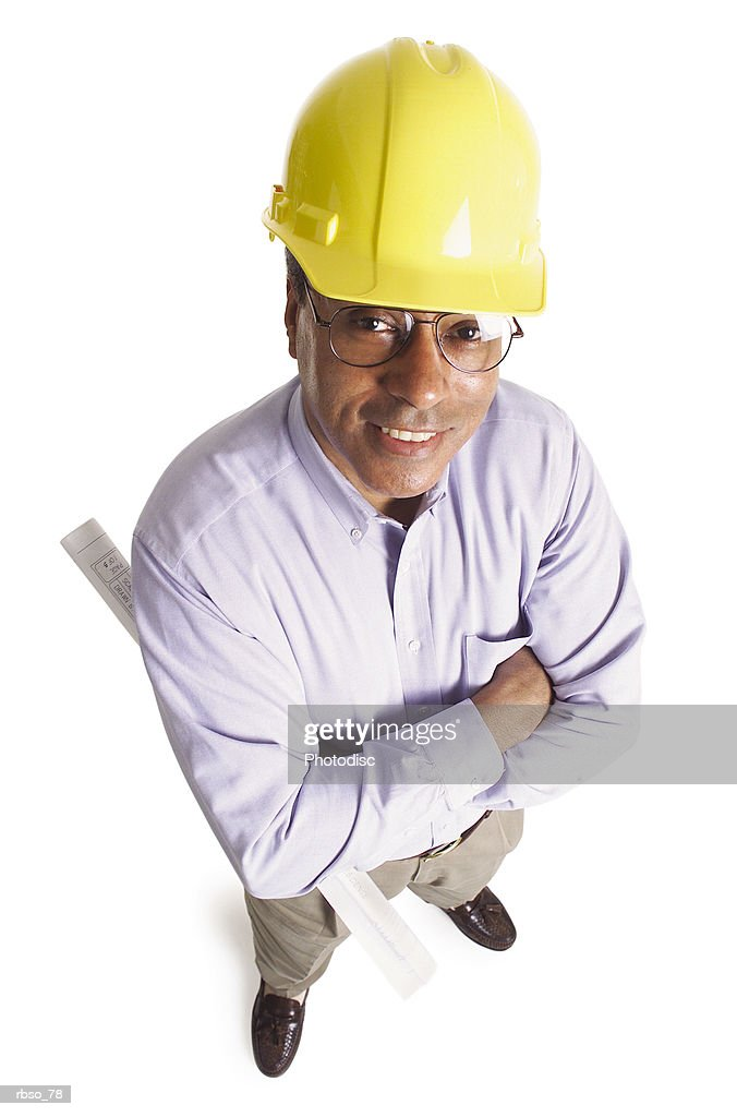 an african american general contractor wearing a hard hat and holding plans smiles as he looks up at the camera : Foto de stock