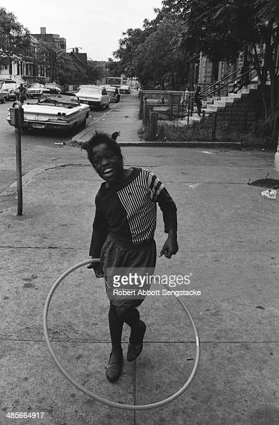 An African American girl twirls a hula hoop while standing outdoors on a sidewalk in the Southside neighborhood of Chicago Illinois mid to late 1960s