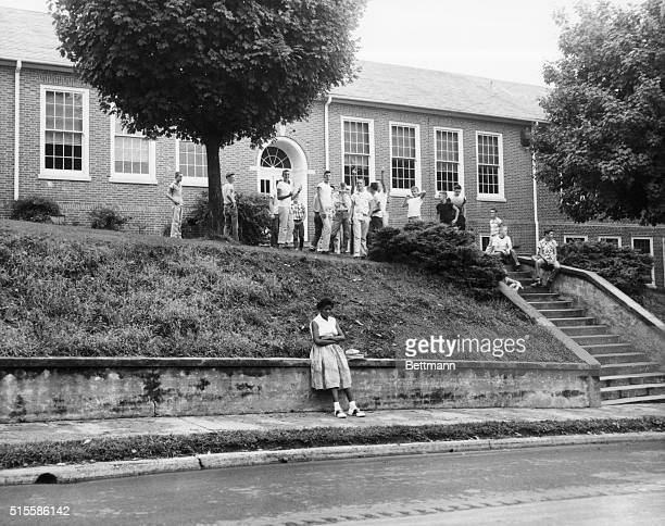 An African American girl waits outside Clinton School as White students look on after the Federal courts ordered the enforcement of desegregation laws