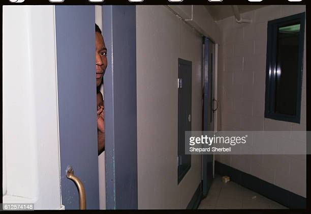 An African American inmate peers through an opening in his prison cell in the Buckingham Correctional Institution | Location Dillwyn Virginia USA