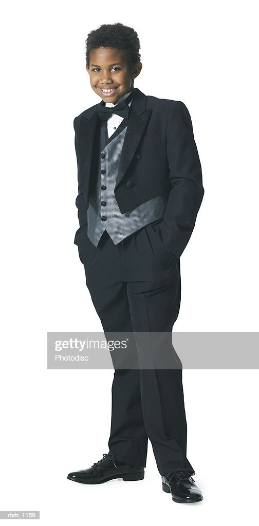 an african american male child in a tuxedo puts his hands in his pockets and smiles : Stockfoto