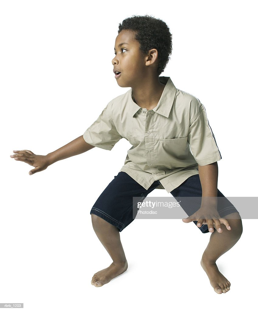an african american male child in black shorts and a tan shirt strikes a fun surfing pose : Stockfoto