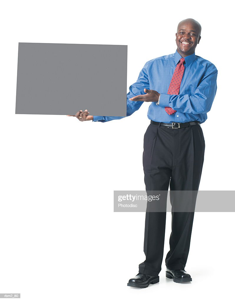 an african american male in black pants and a blue dress shirt holds a blank sign to his side and gestures to it : Stockfoto