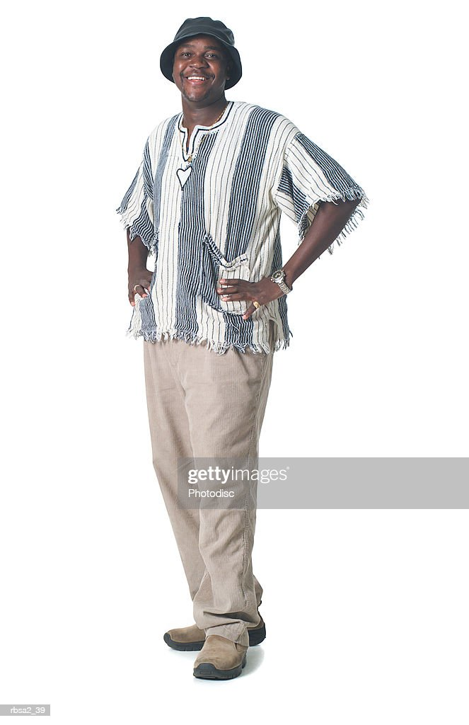 an african american male in tan pants and stripped shirt puts his hands on his hips and smiles at the camera : Foto de stock