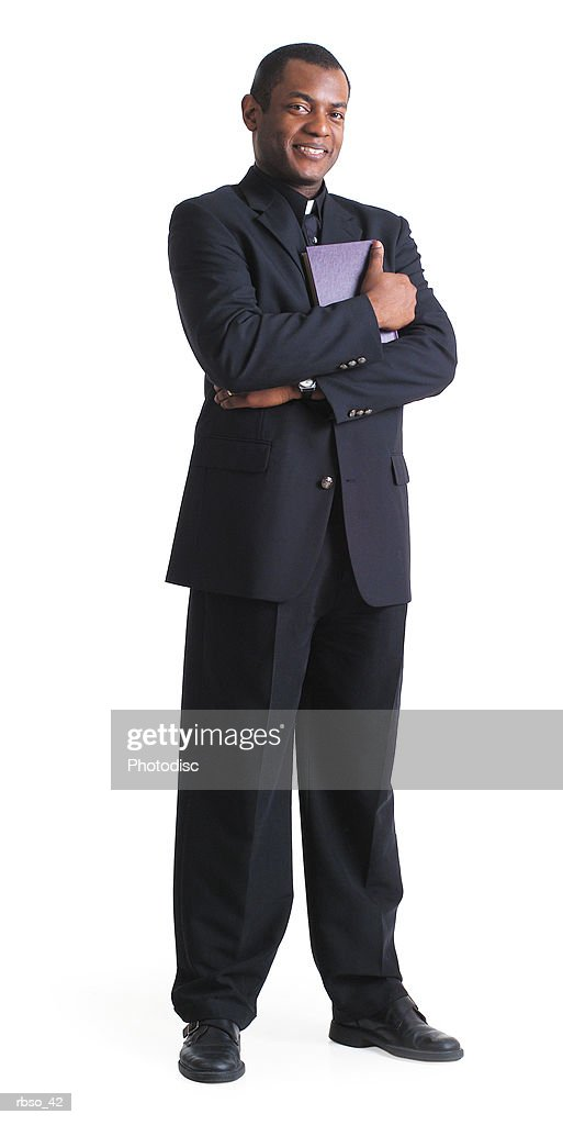 an african american male preacher holds a book and folds his arms : Foto de stock
