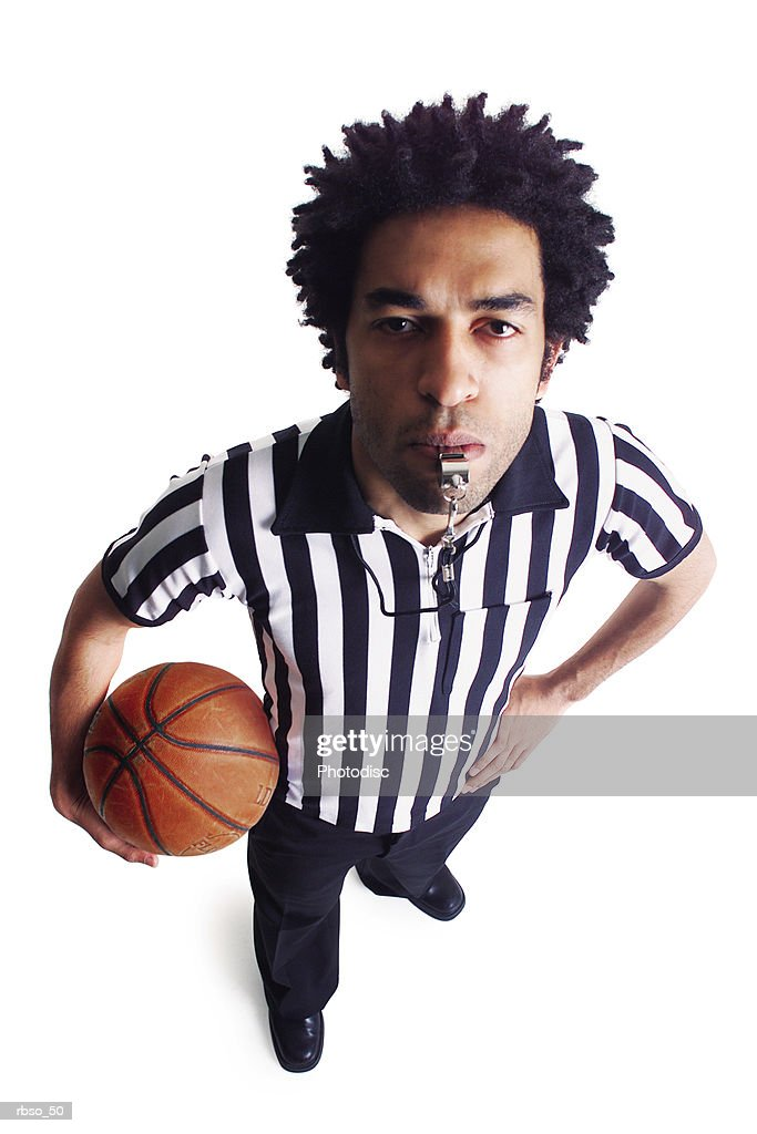 an african american male referee blows his whistle as he looks up at the camera : Foto de stock