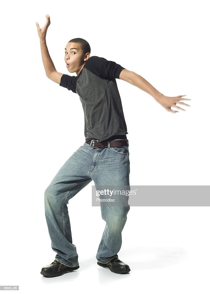 an african american male teen in jeans and a grey shirt does a funny dance : Stockfoto