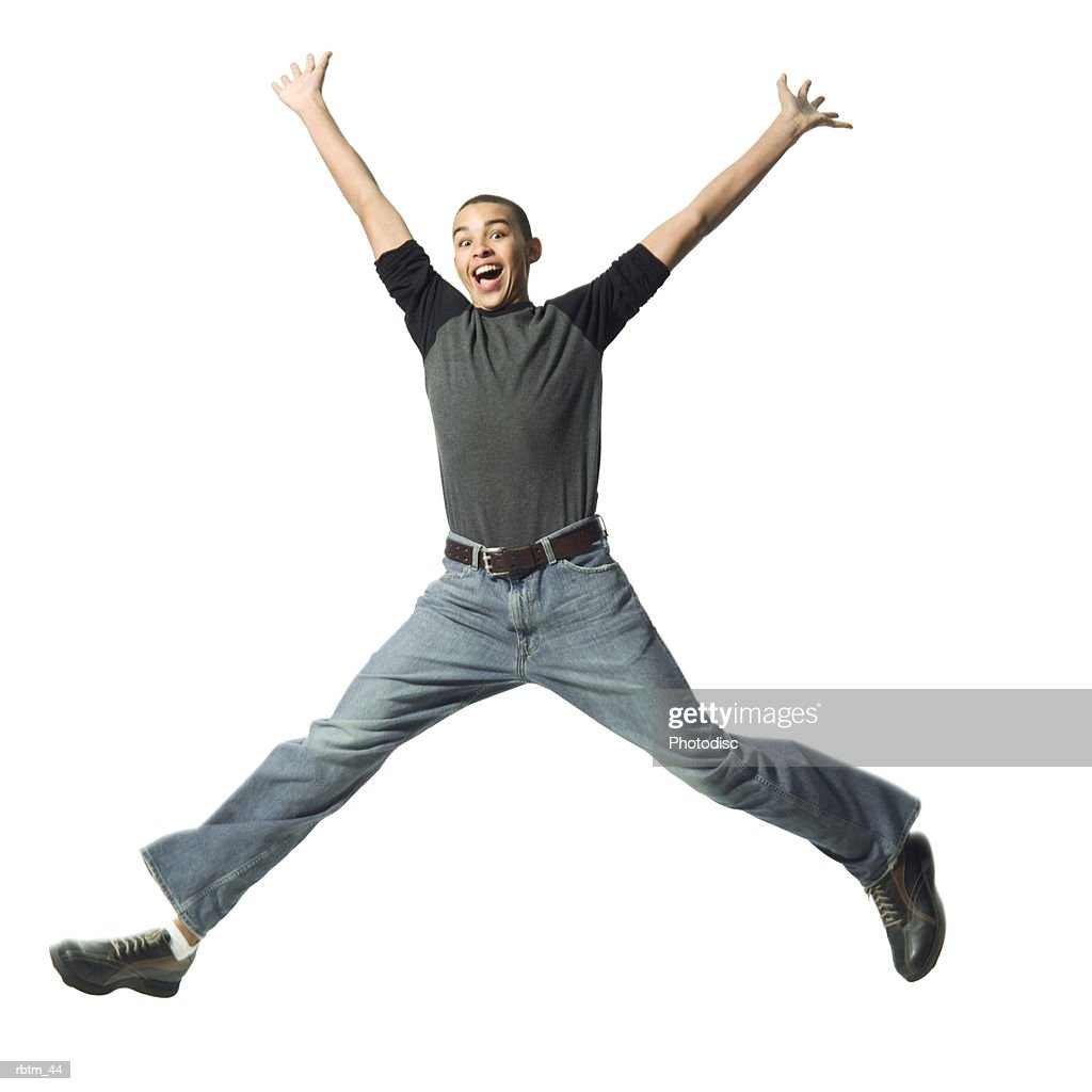 an african american male teen in jeans and a grey shirt jumps up and throws out his arms : Foto de stock