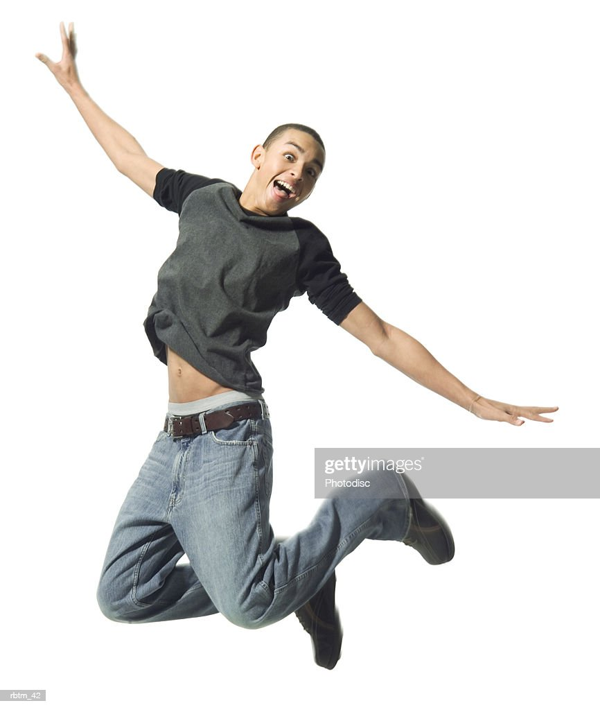 an african american male teen in jeans and a grey shirt jumps up playfully : Foto de stock
