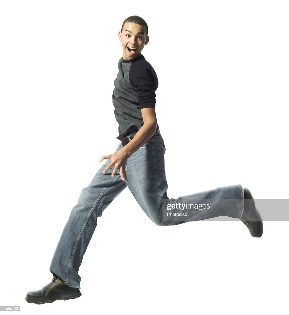 an african american male teen in jeans and a grey shirt runs and jumps : Foto de stock