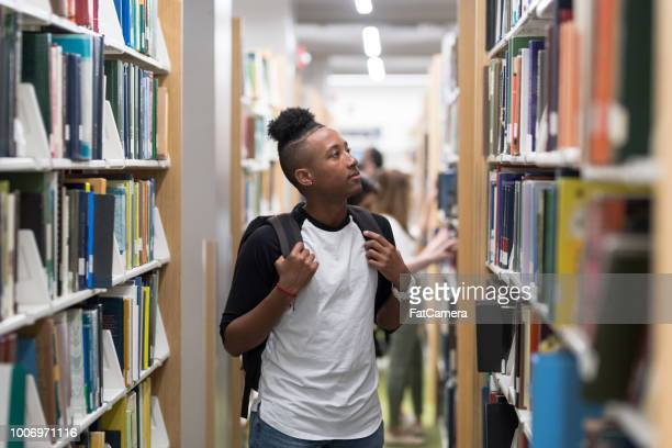 An African American male walking through a university library
