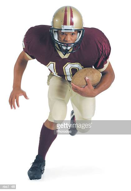 an african american man dressed in a red and white football uniform is holding a football close to him as he leans forward running towards the camera - quarterback stock pictures, royalty-free photos & images