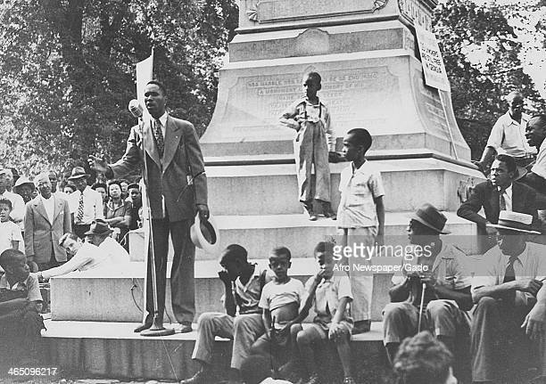 An African American man gestures and speaks to a crowd in front of a monument during a protest against lynching Monroe Georgia August 10 1946 A sign...