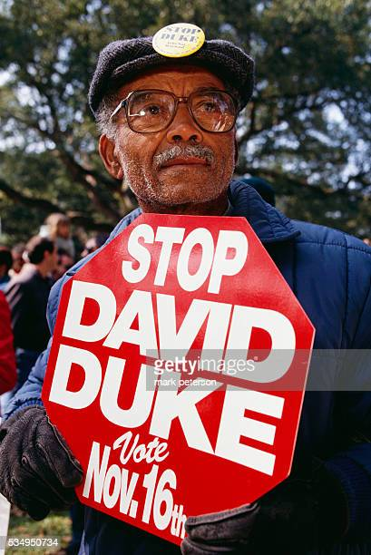 An African American man holds a sign reading Stop David Duke Duke a former Green Dragon in the Ku Klux Klan and proponent of white rights is...
