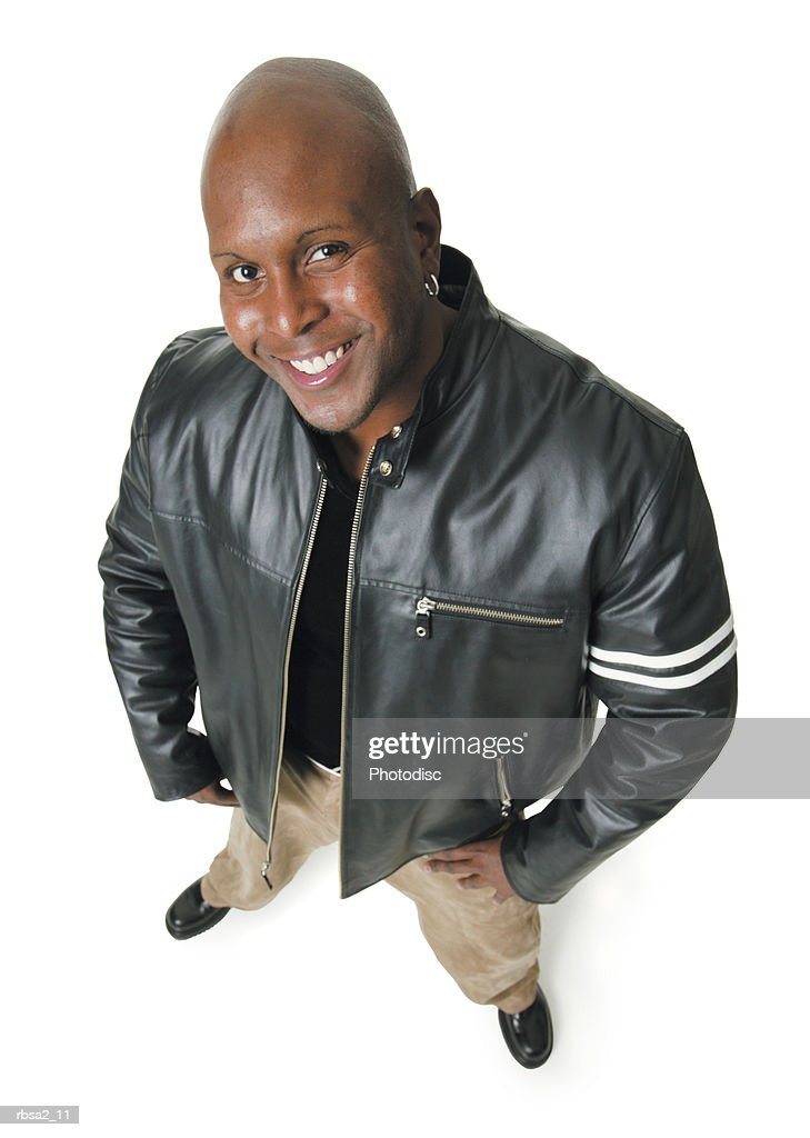 an african american man in tan pants and a black leather jacket smiles up at the camera : Foto de stock