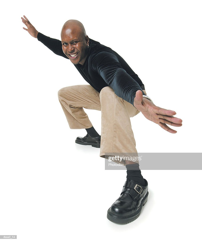 an african american man in tan pants and a black shirt bends down and spreads out his arms in a surfing pose : Foto de stock