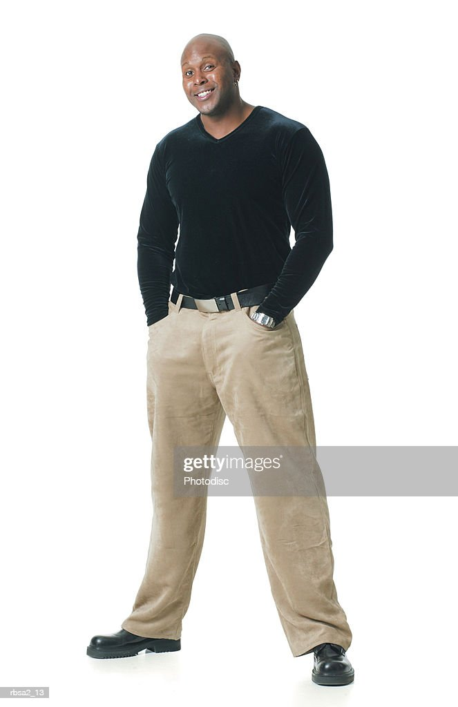 an african american man in tan pants and a black shirt puts his hands in his pockets and smiles : Stockfoto