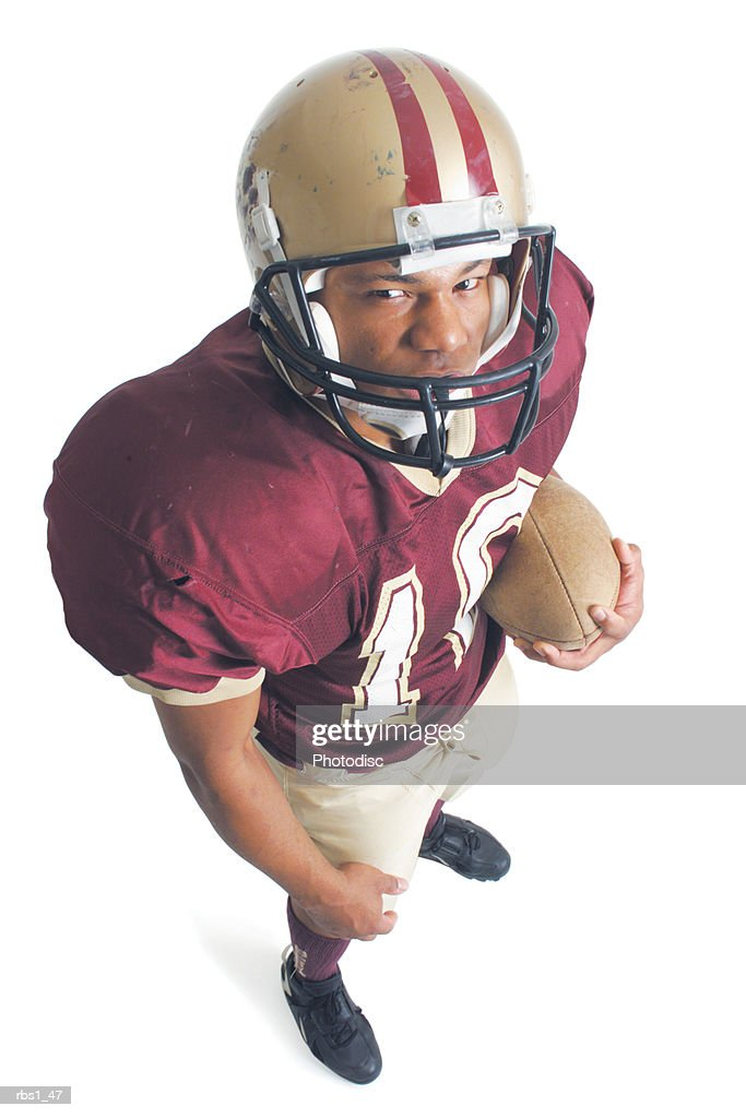 an african american man is standing and wearing a red and white football uniform while holding a football and squinting up at the camera : Foto de stock
