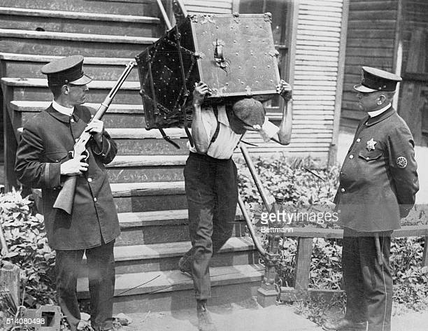 An African American man moves his belongings to a safety zone under police protection during the Chicago Race Riot of 1919