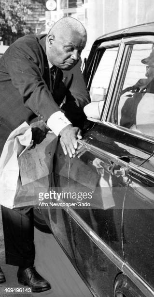 An African American man speaks to a person in a car regarding an amendment to the City Charter calling for desegregation in hotels motels and...