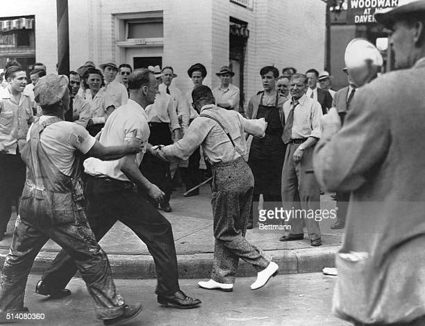 An African American man the victim of assault during Detroit's race riot tries to escape from a mob before further violence ensues