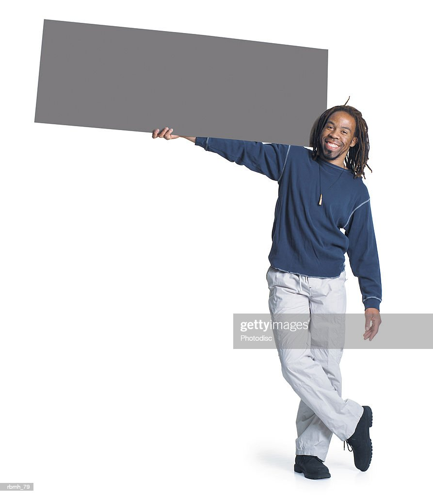 an african american man with dreadlocks wearing kakhi pants and a blue shirt holds a blank sign with one hand and rests it on his shoulder as he stands with his legs crossed : Stockfoto