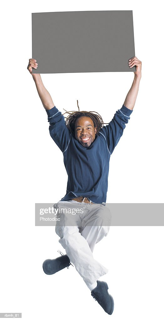 an african american man with dreadlocks wearing kakhi pants and a blue shirt jumps in the air with is legs crossing as he holds a blank sign above his head with two hands : Stockfoto