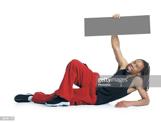 an african american man with dreadlocks wearing red pants and a black tank top lays on the ground propped up on one elbow while his other arm holds a blank sign above him and he smiles - rasta photos et images de collection