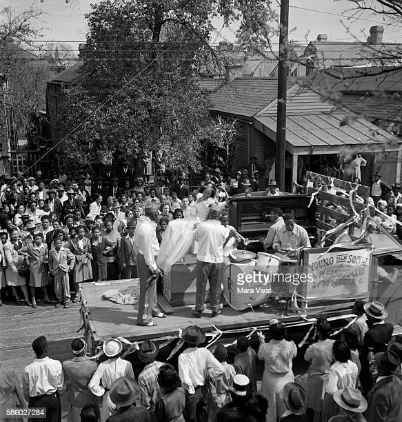 An African American neighborhood gathers to watch a Mardi Gras parade in New Orleans Louisiana circa 1950